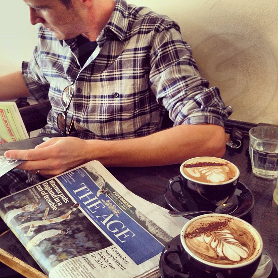 man drinking coffee reading paper photo