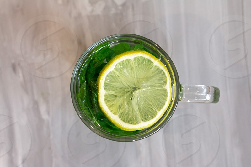 Circle glass cup round lemon hot water hot tea mint minimalistic yellow green herb herbal vitamin flu cold illness vegan food health care healthy vegetarian  top view fruit  photo