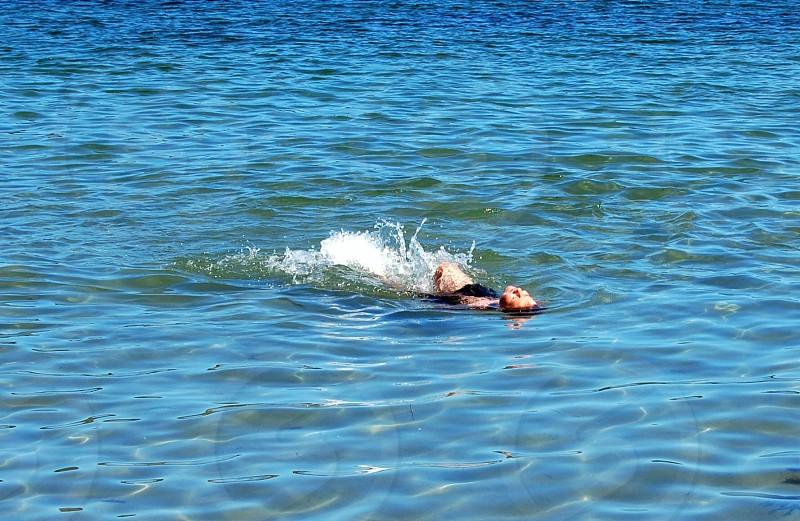 man swimmin on the sea photo