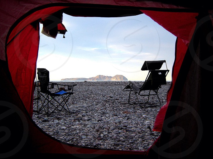 Isolated camping spot on the ocean with a mountain view photo