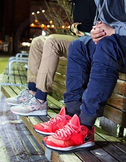 two boys sitting on top of a park bench photo