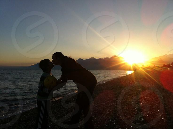 Love mom child kiss sunset beach photo