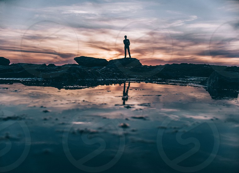 person silhouette standing on a rock over water with a sunset in the distance photo
