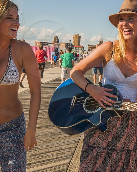 woman in brown hat holding blue acoustic guitar beside woman in grey and white bikini top under white clouds and blue sky during daytime photo