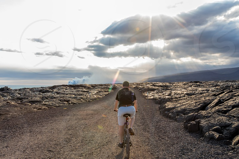 A man riding a bike to see the lava flow in Volcanoes National Park.  Big Island of Hawaii.  Model released. photo