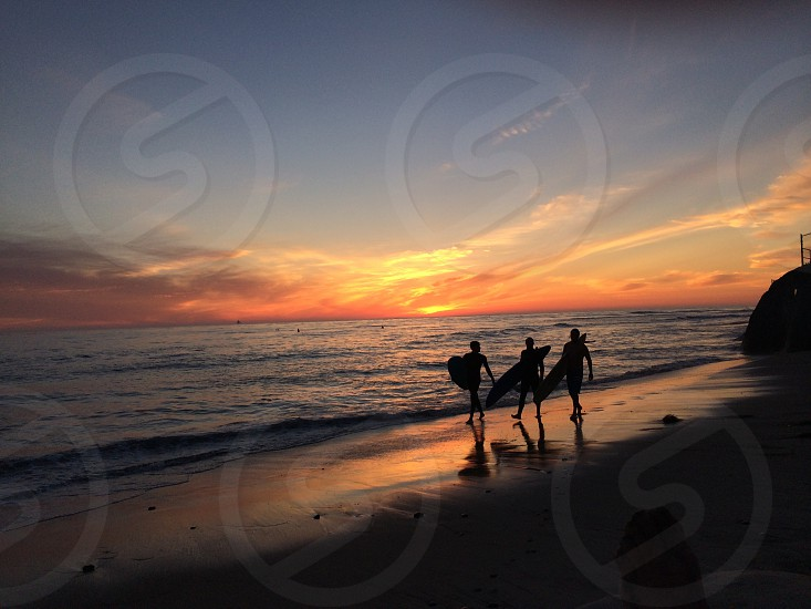three people walking along beach with surfboards in sunset photo