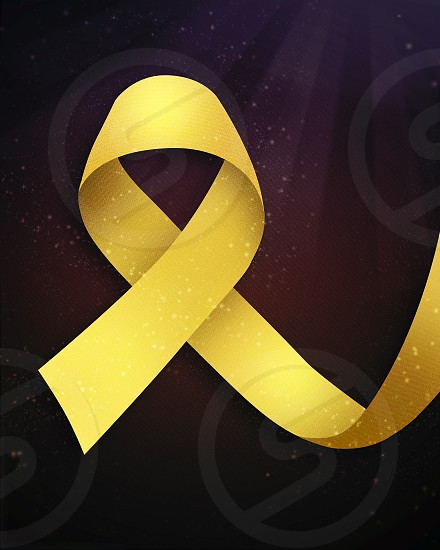 Yellow awareness ribbon symbol of childhood cancer awareness on black background photo