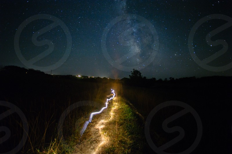 lights on a field path surrounded dark land and trees with city lights in the distance under a milky way starry night sky photo