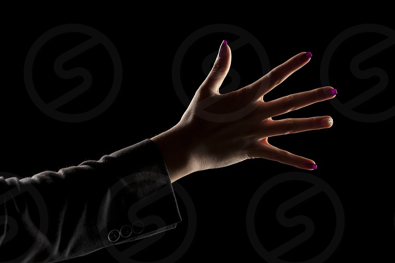 female hand with fingers spread on a dark background photo