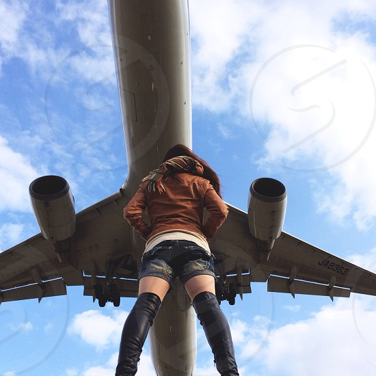 woman in black leather over the knee boots and denim shorts standing under a plane photo