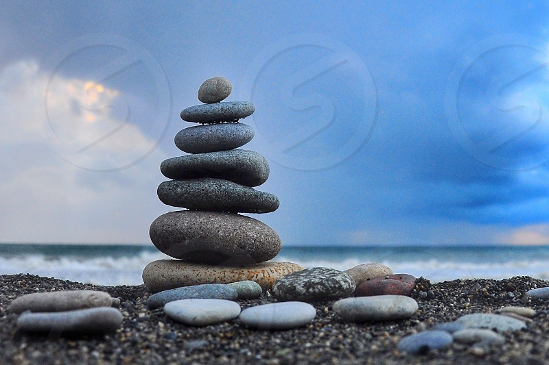 stacked grey flat rocks on beach shore under white cloudy sky during daytime photo