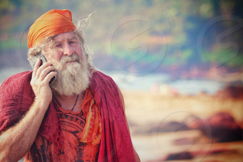 white haired beard using phone by taking to a call photo