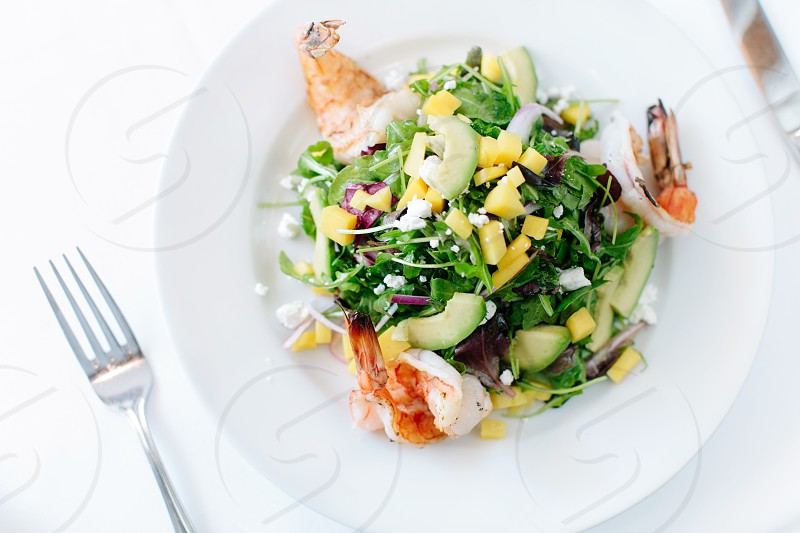 shrimp and fresh vegetable salad on plate photo