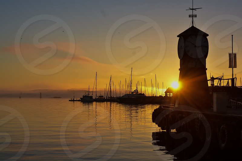 Sunset time in down by the city Harbour -sunset - city - sea - Harbour - boats  photo