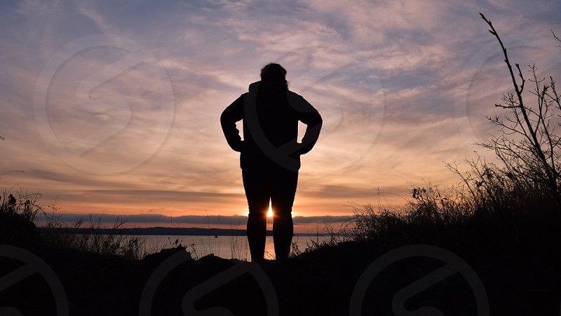 A person looking out towards a sunset photo