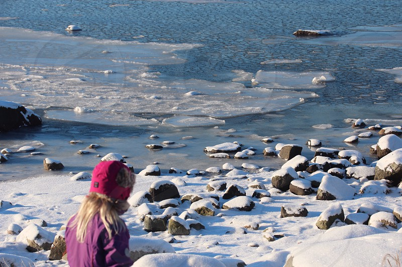 person in purple jacket wearing red knit cap at snow field with brown rocks near body of water during daytime photo