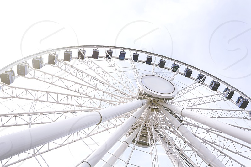 Bottom view of a ferris wheel against a clear sky. Architecture and amusement parks. Fun and tourist attraction photo