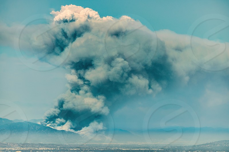 photography of explosion and arising smoke under white and blue sky during daytime photo