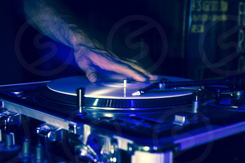 Hands of a DJ while playing vinyl records during a party the hands are moving and are double for a strobe effect of the flash while shooting photo