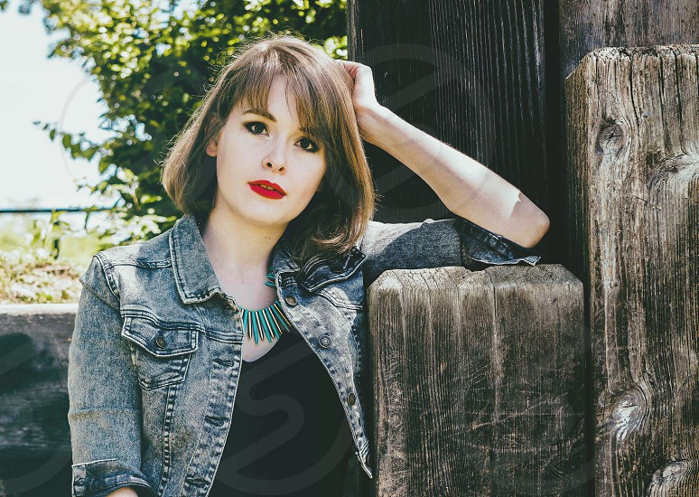 smiling woman in blue denim jacket with red lipstick leaning on brown wooden post during daytime photo