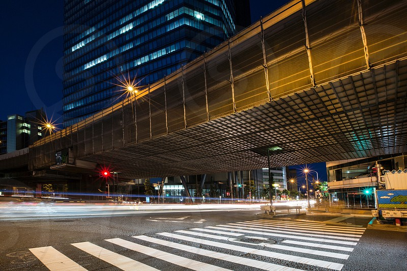 A bridge over a busy road in Tokyo Japan. Light trails trailing off into the dusk. photo