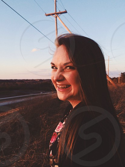 smiling woman near road side photo