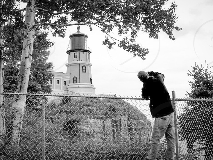 person capturing photo of white lighthouse photo