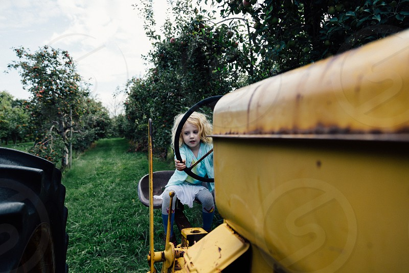 Young girl tractor farm orchard farm photo