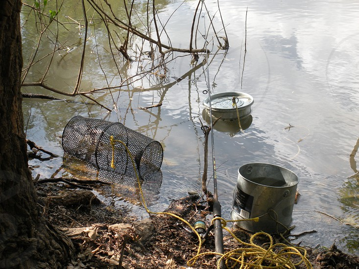 Fishing supplies in use. Fishing fish fisherman fishing pole pole rod and reel rod reel bait bucket bait bucket hunt hunting camp camping camping supplies  photo