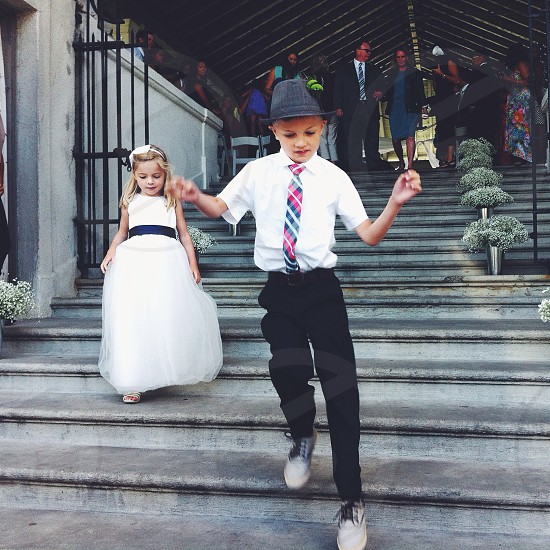boy in white polo shirt walking on stairs near girl in white dress photo