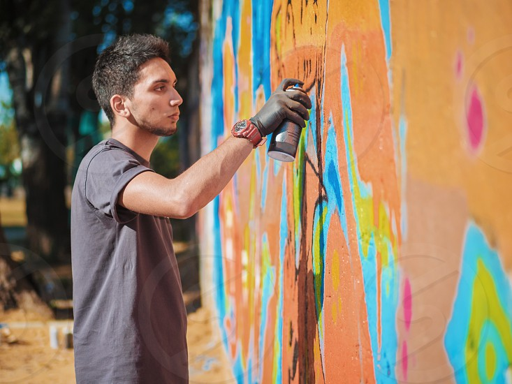 Handsome Talented Young Boy making a colorful graffiti with aerosol spray on urban street wall. Cinematic tonedshot. Creative art. Side view photo