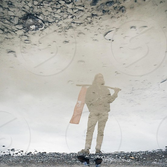 person holding a stick reflected on waters surface photo