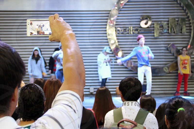 Man filming dance show with a phone. photo