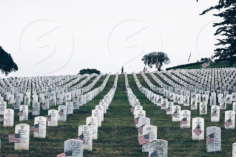silhouette of a person walking in the u.s.a heroes cemetery under blue sky at daytime photo