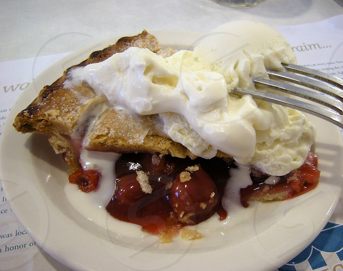 Cherry pie a la mode on white plate with fork photo