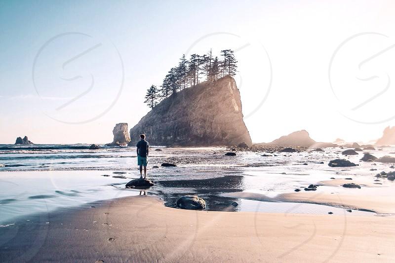 man on beach near pine trees on large rock island tall photo