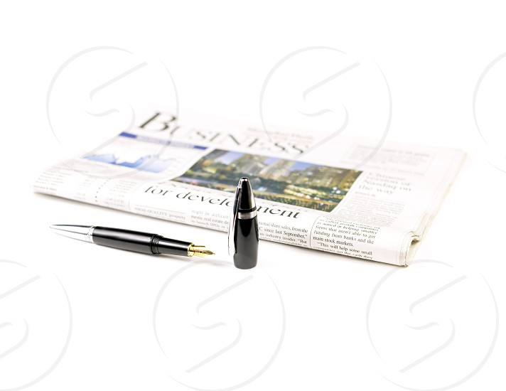 newspaper and pen on white background photo
