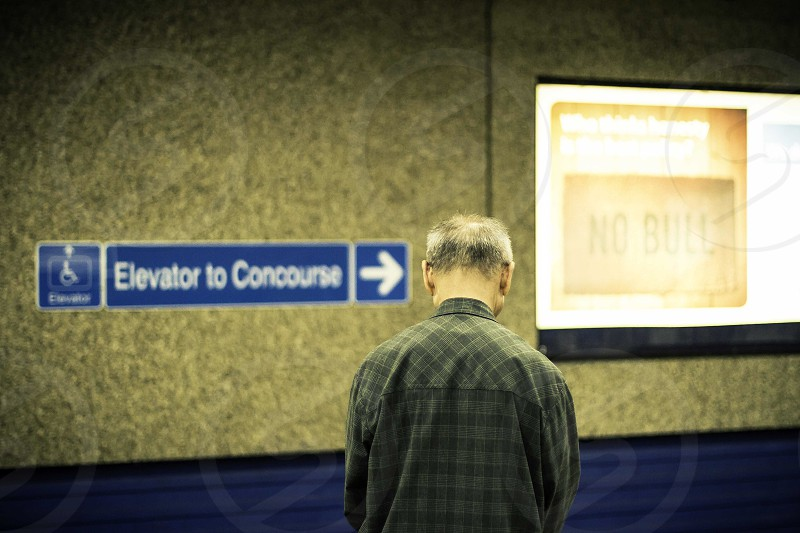 man in grey and black checked dress shirt standing near blue elevator to concourse signage photo