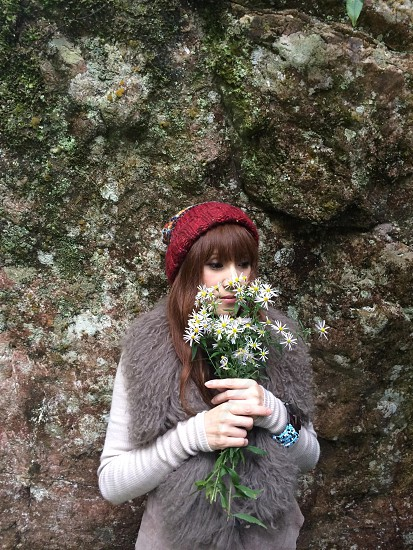 woman in red beanie holding white flowers photo