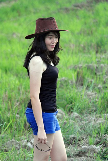 close photo of asian woman wearing a black tank top and blue shorts with cowboy hat in the green grass field photo
