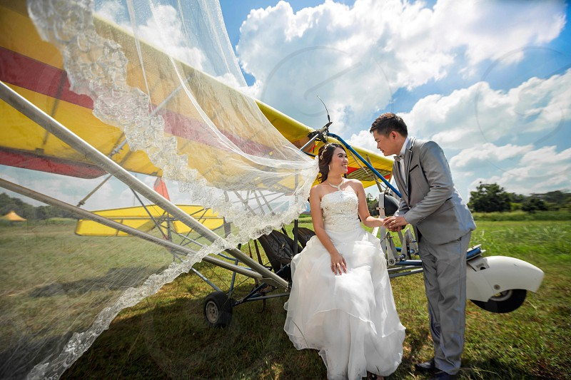 man in gray suit jacket holding the hand of a woman in wedding dress beside airplane photo