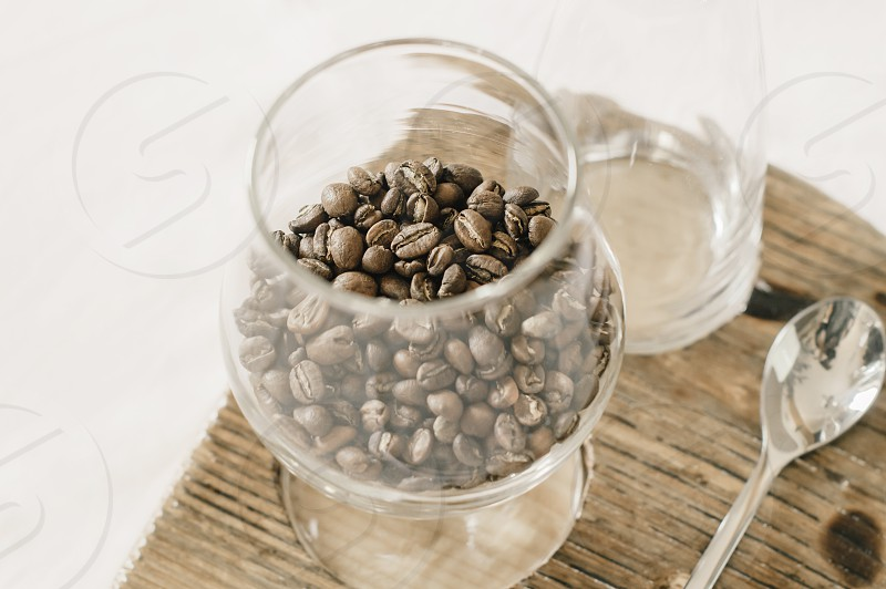 Coffee beans in a glass set on a wooden coaster. photo