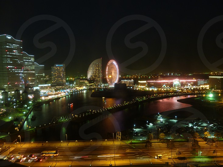 nightscape aerial photography of buildings and bridge near body of water photo