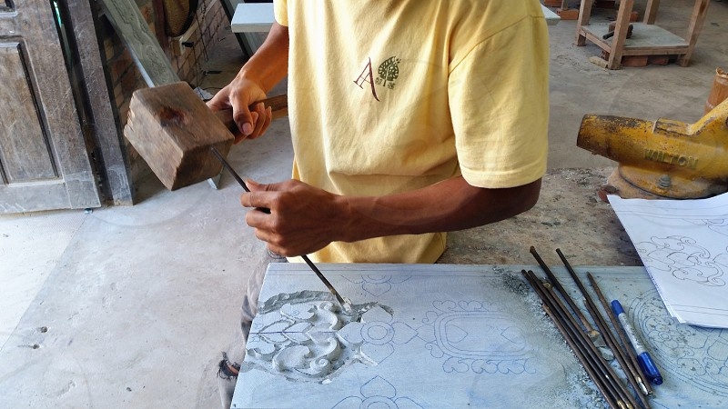 man on yellow t shirt chiseling on white surface during daytime photo