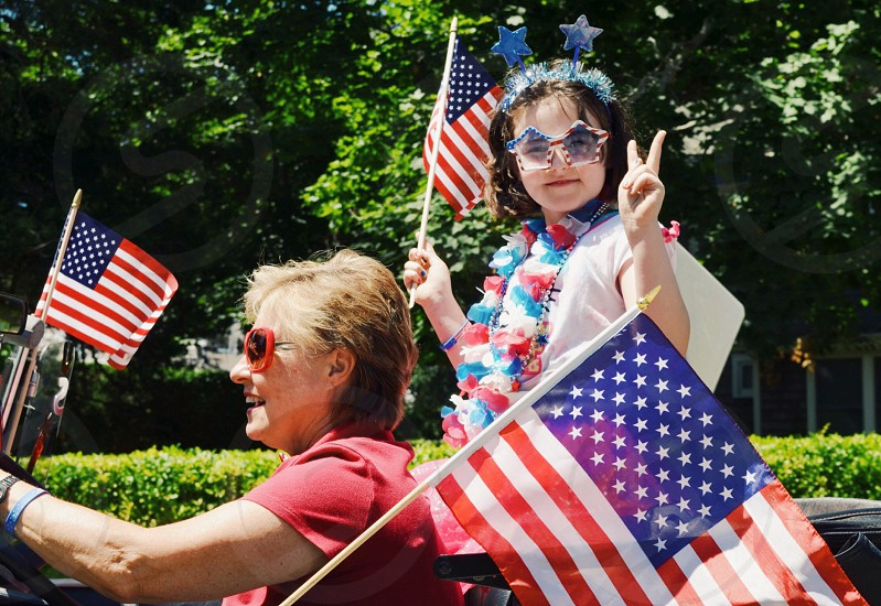 girl in white shirt and flower necklace holding an american flag photo
