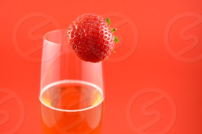 Strawberry with champagne. Glass of champagne with strawberry. Champagne on a red background with copy space for text. Festive golden background. Valentines Day concept photo