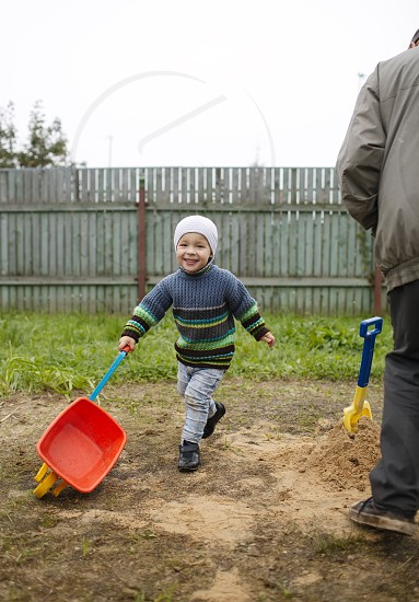 Happy grandson with toy cart runs with grandfather at the countryside photo