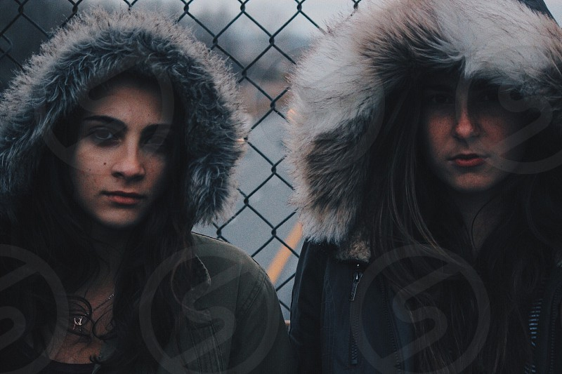 two women in black parka jacket against chain link fence photo