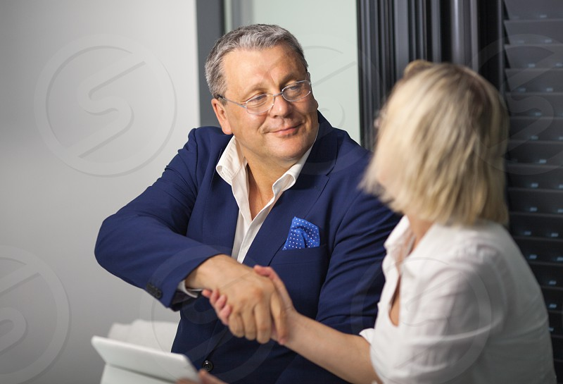 Mature businesspeople having a good deal. Man and woman shaking hands to make a business agreement photo