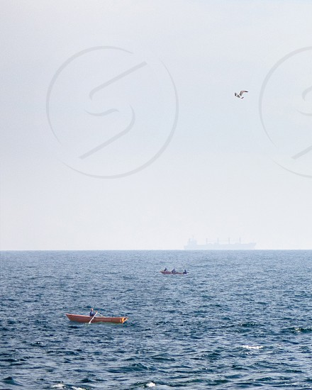 Seascape with fishing boats in an open blue sea and a blurred merchant ship on the horizon at summer day. photo